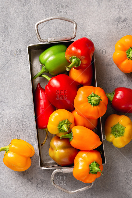 Various washed pepper in sieve served on iron tray overhead view