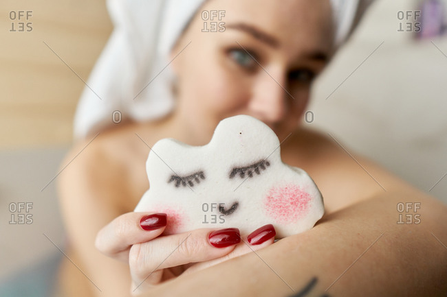 Woman with cloud shaped bath bomb in the tub