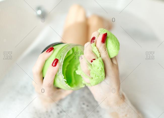 Woman applying skin treatment in the bath