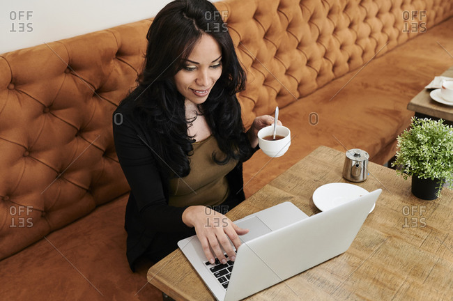 Smiling young businesswoman reading a document on her laptop while working at a table in a trendy cafe