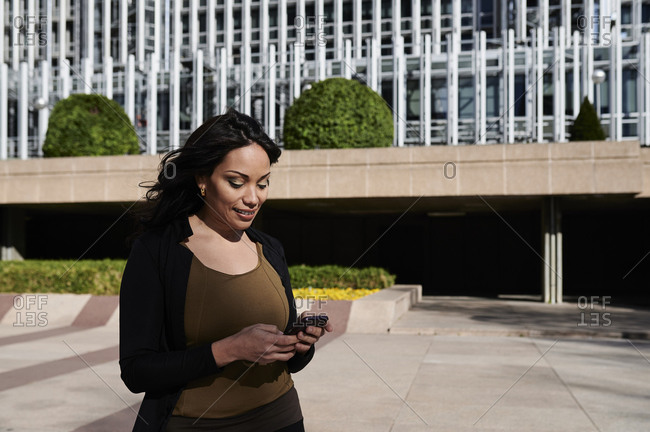 Smiling young businesswoman talking over the phone outside office buildings