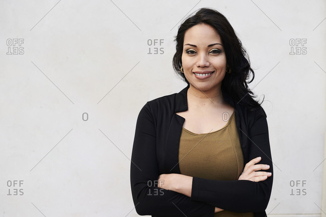 Young Businesswoman with folded arms portrait against white wall outdoors