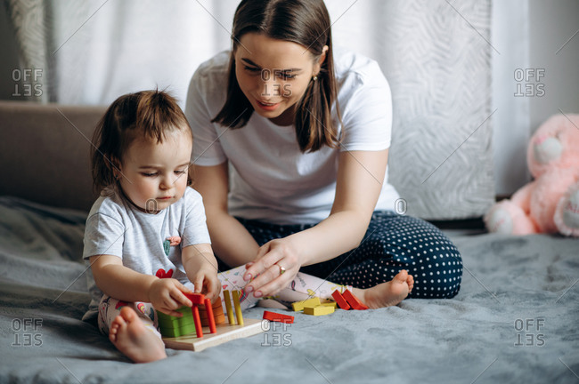 Mom teaches her little beautiful daughter. Earlier development.  Mother plays educational games with her beloved baby girl at home