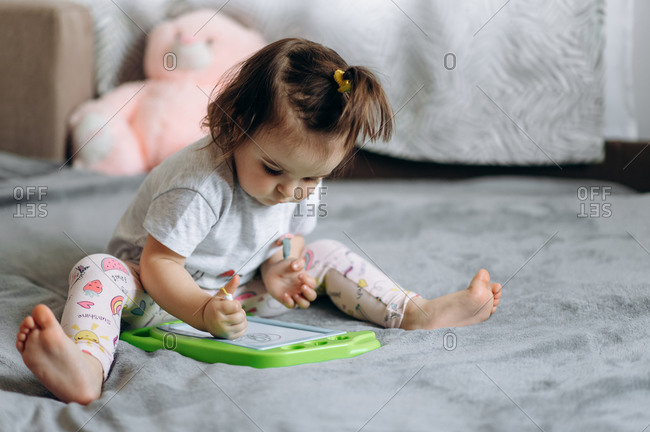 Magnetic drawing board for children. Adorable little baby girl draws on a magnetic board sitting on a sofa at home
