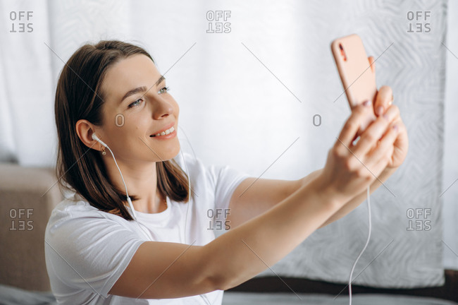 Phone video call. Attractive young woman smiling and communicates via video calling by phone at home on the couch
