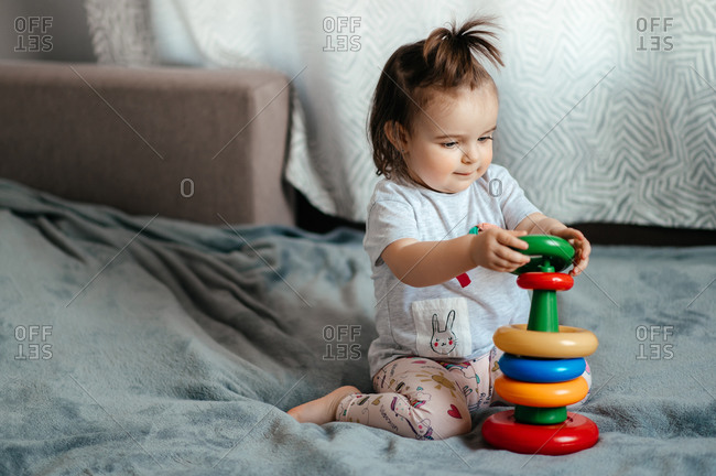Cute blue-eyed little baby girl folds a children's multi-colored pyramid sitting on a sofa at home