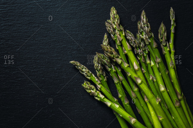 High angle view of wild asparagus on a black slate stone