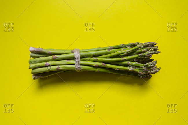 Green asparagus bunch tied with a string on yellow surface