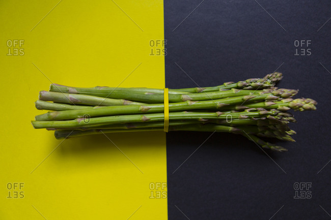 High angle view of green asparagus bunch tied with a yellow rubber band on yellow and black surface