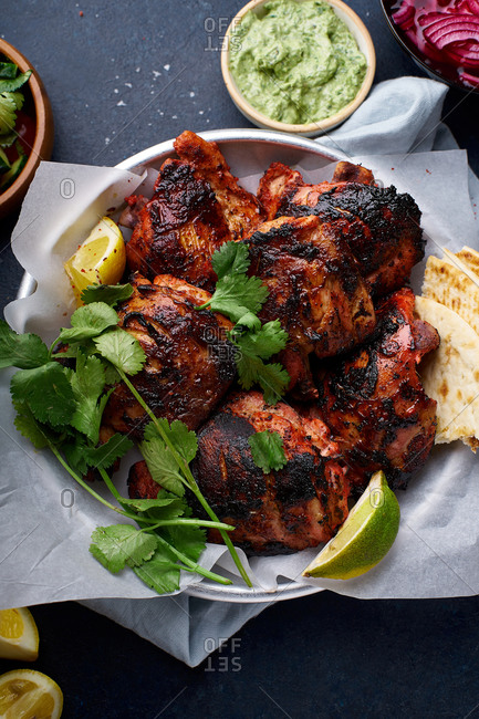 Overhead image of tandoori chicken thighs marinated in tikka sauce, grilled and served with mint chutney. Traditional indian cuisine starter. Dark blue background.