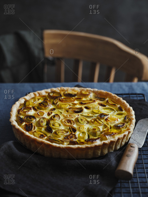 French onion tart on the table covered with linen tablecloth and a blurred wooden chair in the background