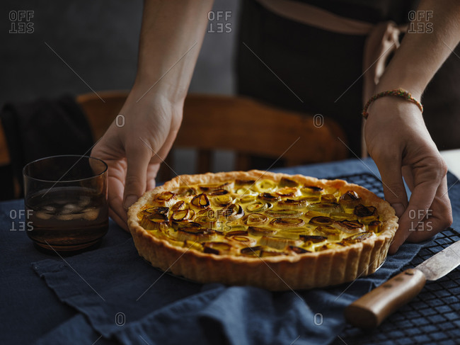 Female hands holding a freshly baked leek tart in cozy home atmosphere