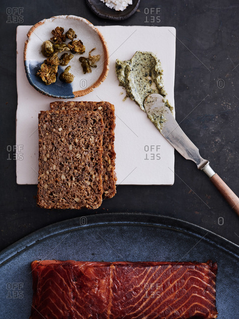 Dark table with various ingredients for making an open-faced sandwich dark - dark brown bread, green butter, smoked trout, capers and salt