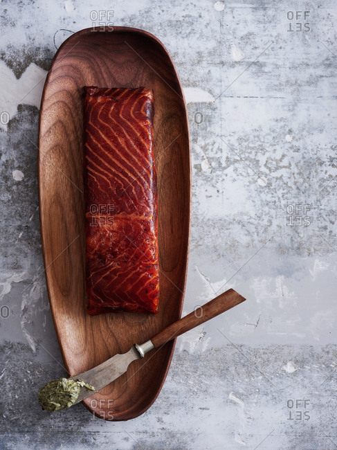 Nordic-styled shot of coffee cured gravlax with nori flavored butter on light background