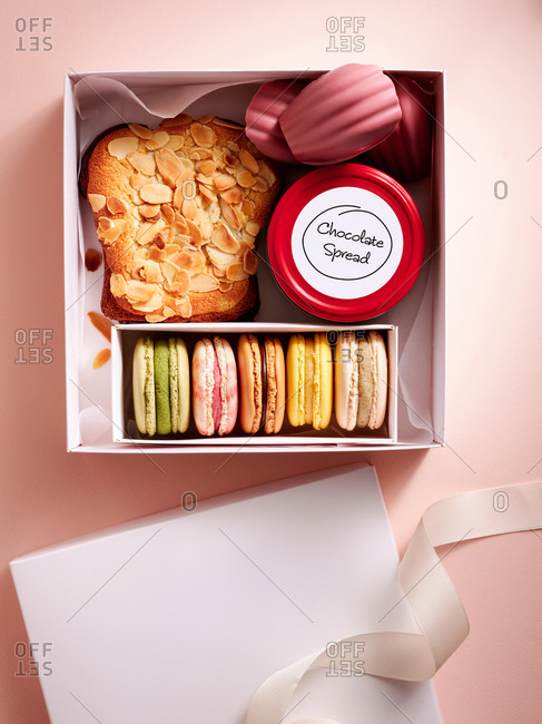 Gift box with assorted desserts: French madeleines and macarons, bostock brioche and chocolate spread on pink background