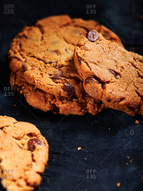 Delicious chocolate chip cookies on dark blue textile background