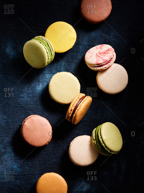 Beautiful assorted flavors of classic French macarons on dark blue textile background