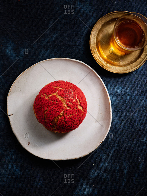 Red raspberry profiterole on beautiful ceramic plate with a cup of tea on dark textile background