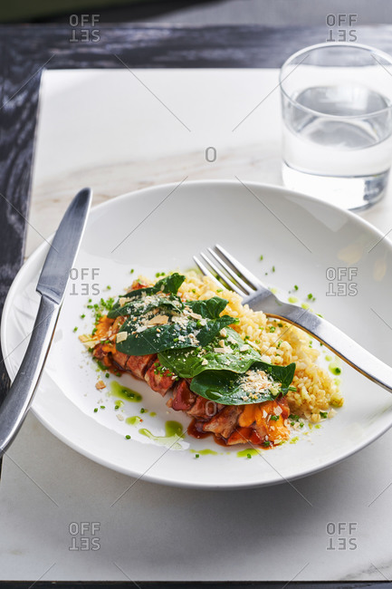 Vibrant dish of Mediterranean chicken and bulgur on light marble background