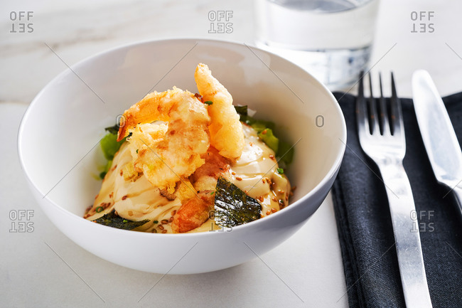 Oriental-style appetizing dish with fried shrimps, cucumbers, avocado and seaweed