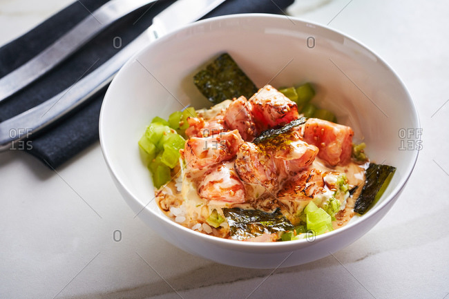 Poke bowl with salmon, pickled cucumber and seaweed