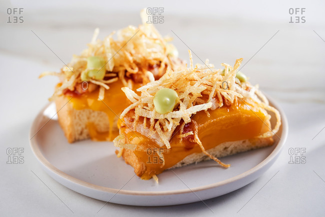 Brioche bun canapé topped with cheddar cheese, crunchy bacon and wasabi mayo