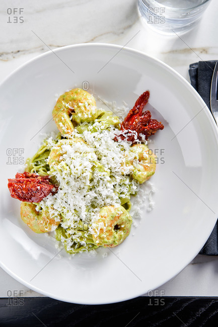 Creamy basil pesto tagliatelle with prawns and sun dried tomatoes on light marble background