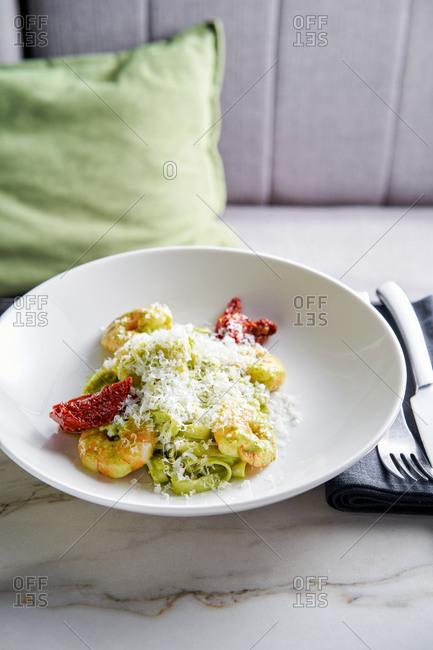 Beautifully plated green pesto tagliatelle with prawns and sun-dried tomatoes