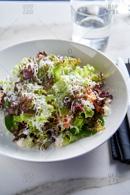 Simple lettuce salad with grated cheese on light marble background