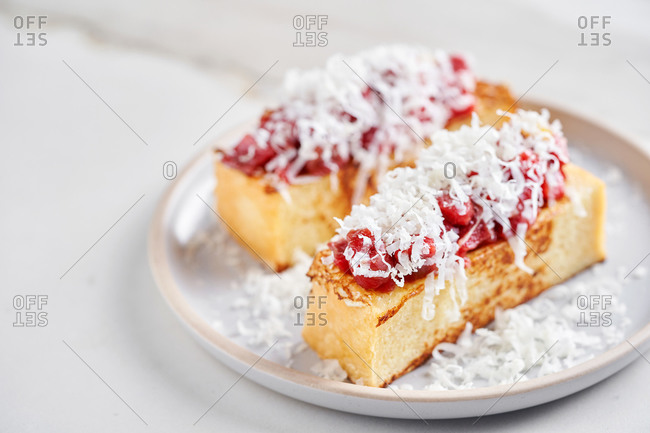 Grilled sourdough toasts with beef tartare and cheese on light marble background