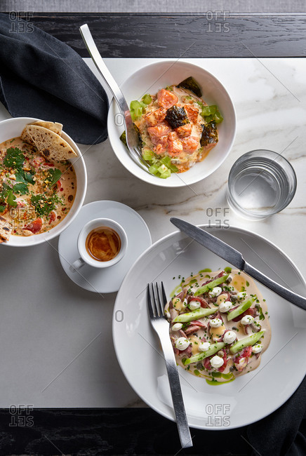 Vertical flatlay of three contemporary plated appetizers in a restaurant setting