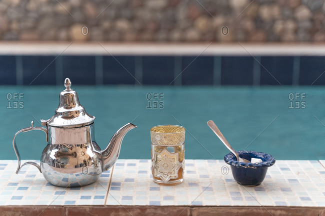 Silver tea pot- tea glass and sugar bowl on poolside