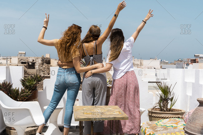 Back view of three young women standing on roof terrace showing victory signs- Essaouira- Morocco