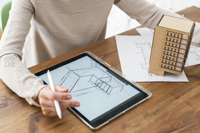 Woman working on architectural model and digital plan on desk in office