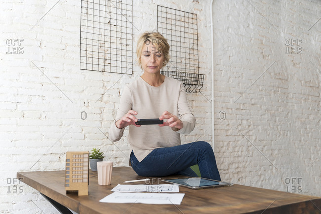 Mature woman sitting on desk in architectural office taking cell phone picture of construction plan