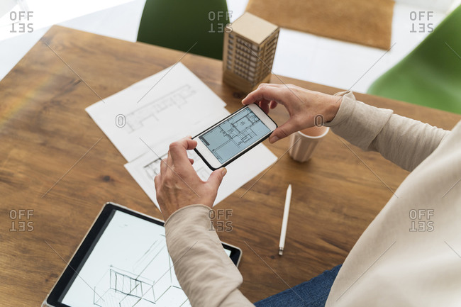 Close-up of woman in architectural office taking cell phone picture of construction plan