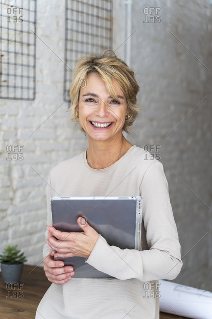 Portrait of smiling mature woman in office holding graphics tablet