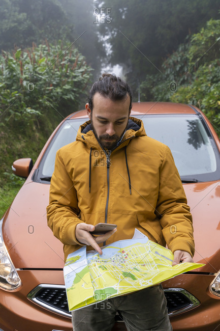 Man with smartphone and map outside car on forest road- Sao Miguel Island- Azores- Portugal