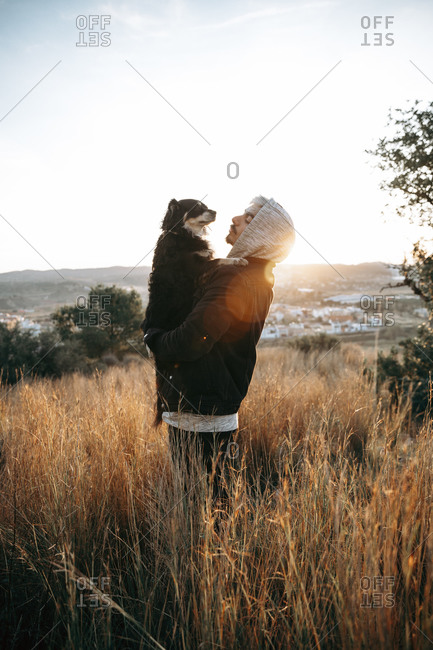 Young man with his dog during sunrise- Montroy- Spain