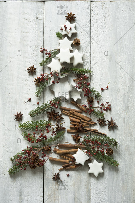Star shaped cookies- cinnamon sticks- fir twigs- star anise- cookie cutters- pine cones and rose hips arranged into shape of Christmas tree