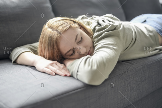 Portrait of blond young woman napping on the couch