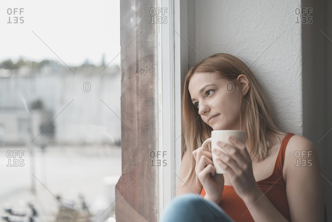 Portrait of pensive young woman with cup of coffee looking out of window