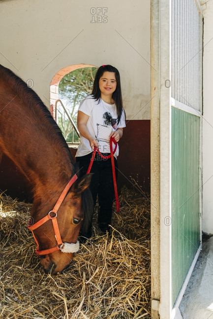 Teenager with down syndrome taking care of horse and preparing horse to ride