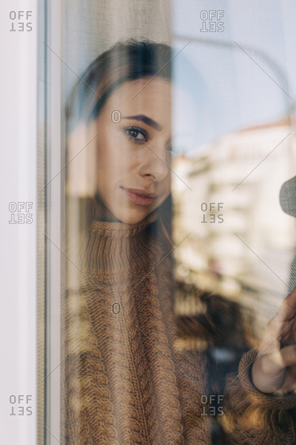 Portrait of young woman behind windowpane