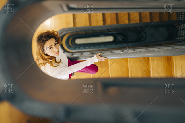 Portrait of young woman in staircase looking up