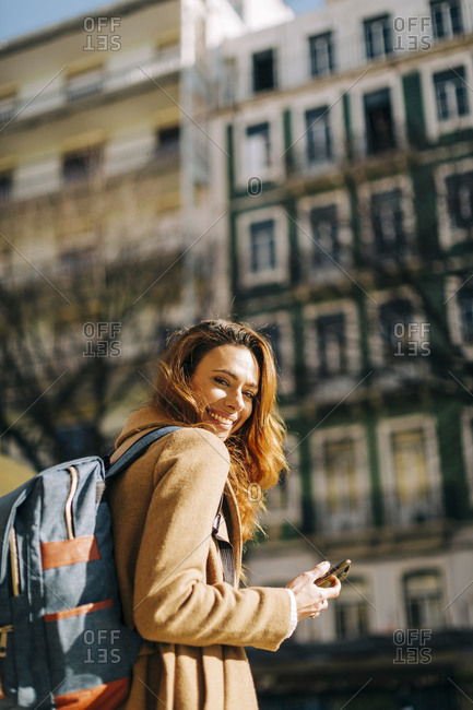 Portrait of happy young woman with backpack in the city- Lisbon- Portugal