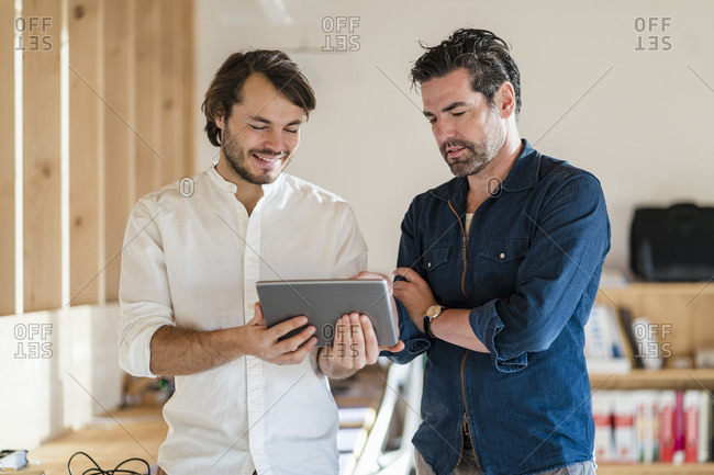 Two businessmen with tablet talking in wooden open-plan office