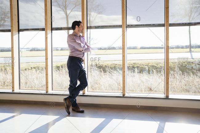 Businessman looking out of window in open-plan office