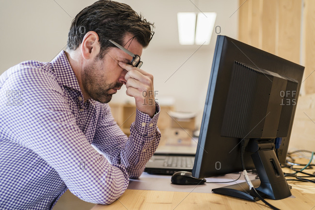 Tired businessman at desk in wooden open-plan office