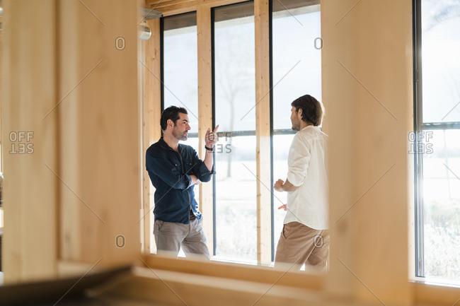 Two businessmen talking at the window in wooden open-plan office